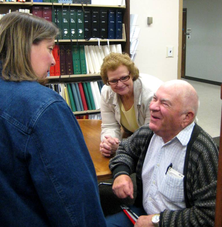 Image: An older man seated at a table with a white cane folded in his hand is talking to two women.