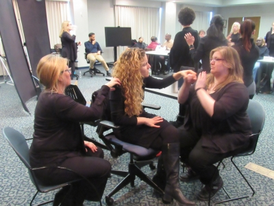 Image of a deaf-blind woman seated receiving tactile sign language from an interpreter seated in front of her.  There is a second interpreter behind her providing her with visual and environmental information. They are in a large conference room with people various types of communication going on.