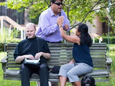 3 people are shown outside.  2 are seated on a wooden swing and 1 is standing behind the swing.  The man behind the swing is holding the hand of the woman who is seated and they are using tactile ASL to communicate.  There is a dog seated at her feet.  The other man is seated beside the woman and he is using a portable refreshable braille display.