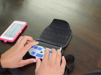 An image of a woman's hands typing on a portable braille display. An iPhone is on the table as well.