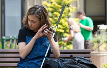 Woman sitting on bench with mobile device and cane.