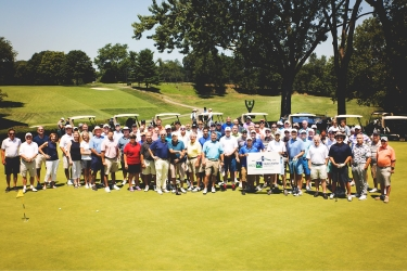 Image description: A large group of golfers stand together, overlooking a large course and golf carts.
