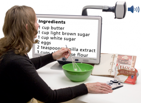 A woman is seated holding a wisk in a bowl with a recipe book open in front of her and a bag of flour to her right.  She is facing a large screen CCTV. The screen has a magnified version of the recipe in the book.  There is a rectangular device above the screen with a sound icon.