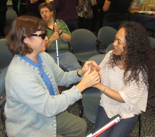 Two woman seated face to face. One is wearing glasses and has both of her hands placed on top of the other woman's hands as she is signing.  The other woman has a white cane in her lap. There is a man in the background with a white cane.