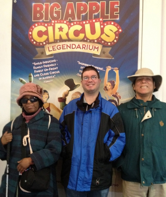 One woman and two men pose in front of a poster for the Big Apple Circus