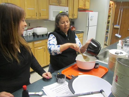 Two women stand at kitchen counter. Woman on right is pouring something from one bowl to another.
