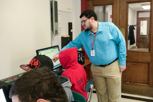 Photo of a man wearing a light blue button down shirt standing over a student using a computer and pointing to a portion of the screen.