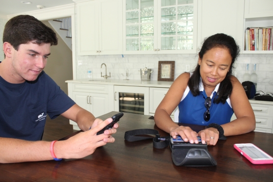 A younger man is seated at a table typing into his iPhone. A woman is seated to his left reading her braille display with her iPhone on the table next to her.