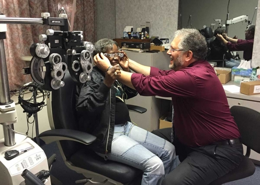Man fits woman for corrective lenses. Woman sits in chair