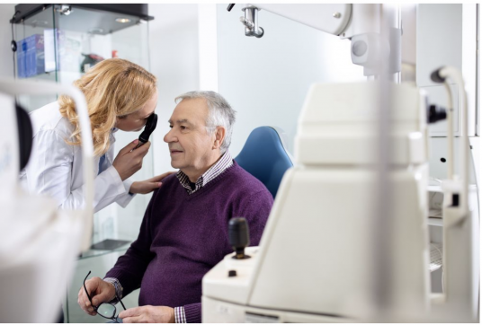 {Image: A man is sitting in a chair in a medical setting.  A woman wearing a white lab coat is leaning in close to the man's right eye with an eye exam instrument held up to her eye.}
