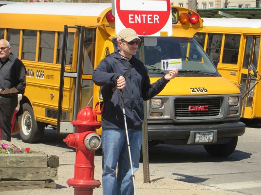 Man stands by stop sign in front of bus with cane and crossing card.