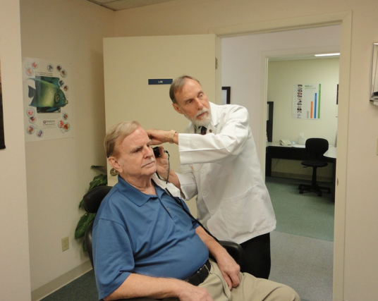 Image: an older man seated in a chair in a doctors office. A doctor is placing an instrument in his ear and both men are looking straight ahead.
