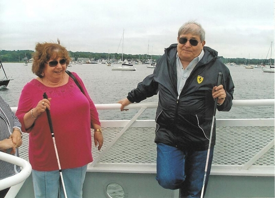 Man and woman with canes standing by the railing on a boat.