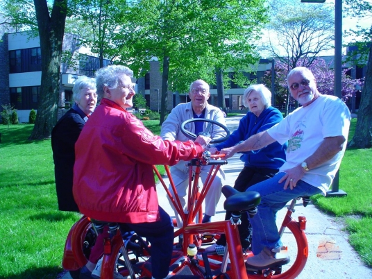 Five older adults are sitting on bicycle with five seats in a circle.  They are all holding the wheel that is in the center.  They are outside on a path and are surrounded by trees and grass.