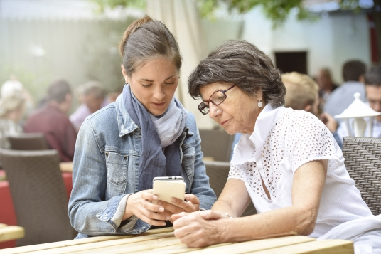 A younger woman is seated at a table next to an older woman. The younger woman is holding an iPhone. Both women are looking at the phone.