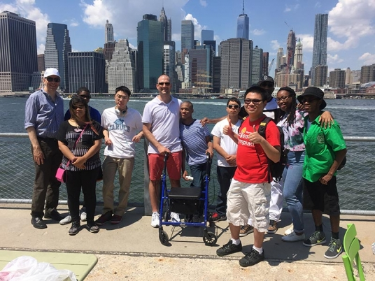Students pose with NYC skyline behind them.