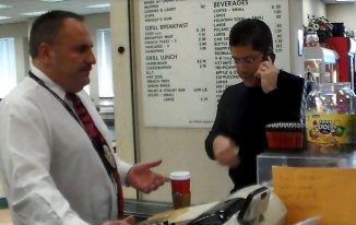 Man at cash register with hand out, standing across from a man with a cell phone in one hand and money in other hand; a cup of coffee is on the counter between the men.