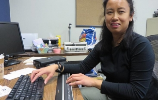 Woman sitting in front of braille display and keyboard.