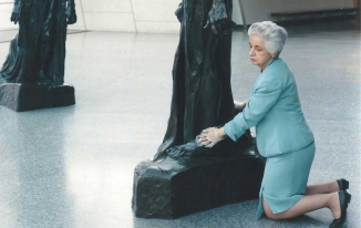 Woman kneeling next to statue to touch it.