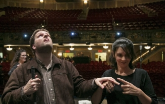 man stands in theater with woman by his side