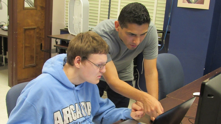 Photo of a man wearing a blue sweater (left) being instructed by a man wearing a gray t-shirt (right) as he points to a laptop monitor