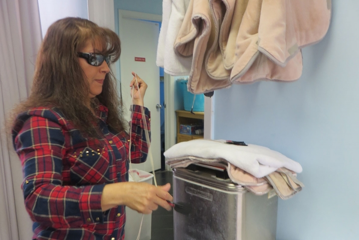 Woman in glasses standing in front of towel warmer at physical therapy clinic.