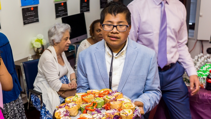 Photo of a young man wearing a white button down shirt and light blue suit coat holding a platter of sandwich wraps
