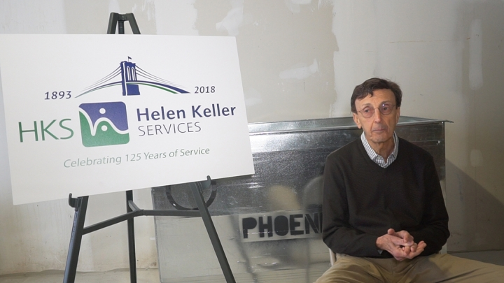 Photo of a man wearing a black sweater sitting in a large gray room with a poster with the Helen Keller Services logo sits next to him.