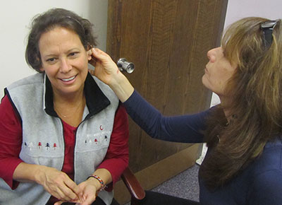 Audiologist looks in woman's ear.