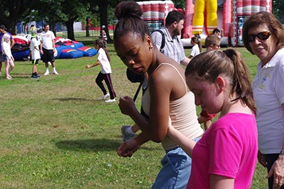 Two girls walking together on grass; inflatable bouncers and other people walking and playing in the background