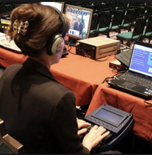A woman is sitting with her back to the camera facing a table with an open laptop comput-er.  She is holding a small black electronic device in her lap and her fingers are resting on the keys.  She is wearing large headphones over her ears.