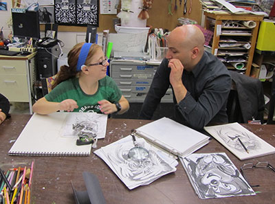 Girl and man sit at table talking. Table is filled with drawings, paper