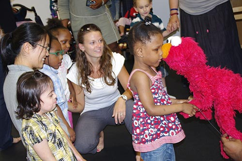 Girl nuzzles Elmo puppet and holds puppet's hand; on the left, four other children and an instructor are watching and waiting to greet Elmo.