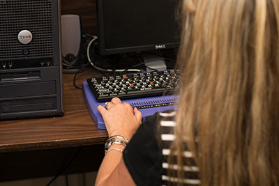 Woman using refreshable braille display; her back is to the camera.