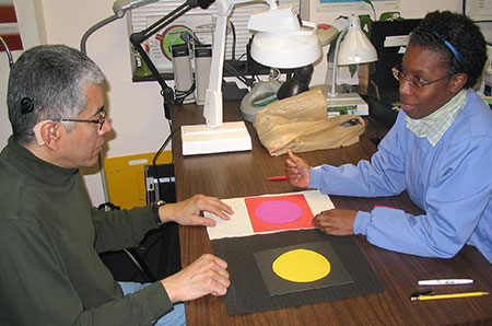 A man and a woman sit on opposite sides of a desk. Between them are pieces of paper with different color circles on contrasting backgrounds.