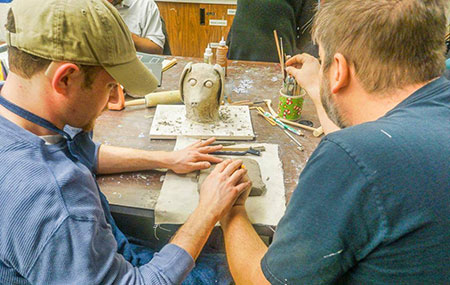 Two men with their backs to camera work together on a sculpture. Their hands are touching as they touch the clay. Just past their hands is a small sculpture of a dog's head facing camera. On the right is a cup filled with artist tools.