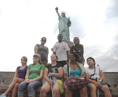Youth Program participants pose in front of the Statue of LIberty.