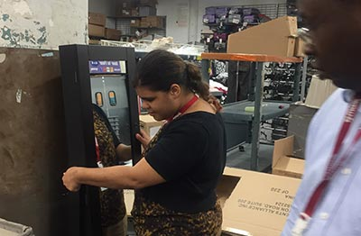 Girl fixing mirror in TJMaxx warehouse as supervisor looks on.