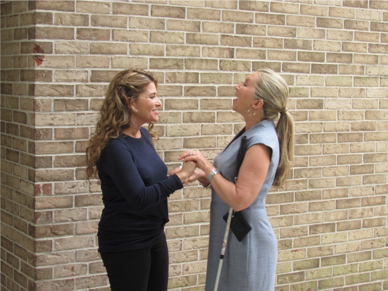 Two women facing each other. One woman is speaking and has her hands placed on the other woman's hands to receive sign language.  She has a white cane under her arm.  The other woman is signing yes and smiling.