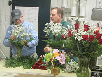 Man creating a flower arrangement as his supervisor looks on