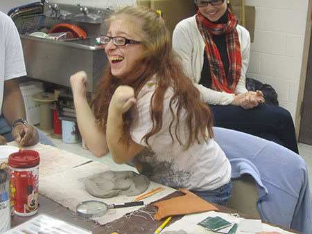 Girl laughs as she puts her elbows in clay.