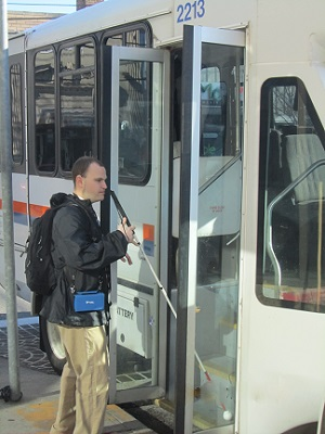 Man holding a cane enters a bus