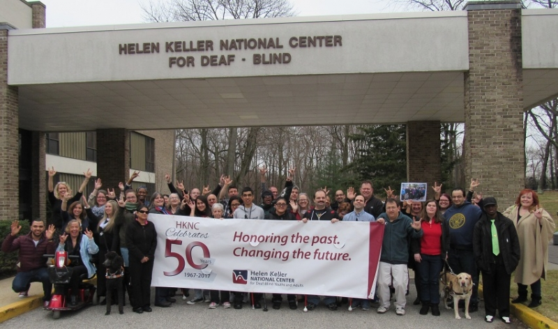 "A group of men and women standing under a portico which says Helen Keller National Center for Deaf-Blind.  They are holding a large maroon and white banner with the number 50 on it and the words ""HKNC Celebrates 50 years. 1967-2017. Honoring the past. Changing the future."""
