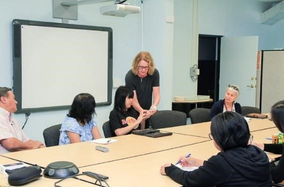Cathy, standing, teaches deaf-blind awareness to agency personnel