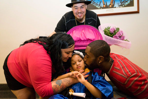 Cynthia and Danny Ramos and Arnold Campell congratulate 4-year-old Winter Ramos for graduating from Helen Keller Services for the Blind's preschool on Friday.