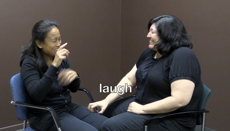 "Two women signing, the word ""laugh"" is written on the picture"
