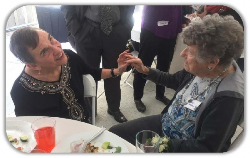 At the October Brunch celebrating HKNC's 50th Anniversary, Michelle Smithdas (L), the first deaf-blind instructor at HKNC (1979 - 2010), talks to Vera Schiller (R), the first HKNC regional representative from the California office (1976 – 1980)