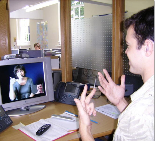 A man is sitting at a desk and is communicating with a person on a computer screen.