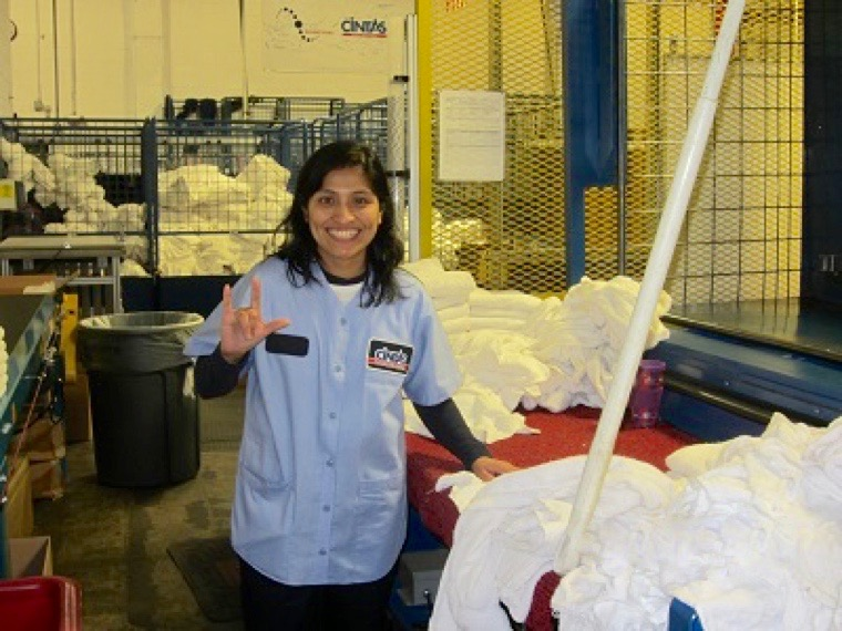 """Woman in uniform smiling standing in an industrial laundry room.  She is smiling at the camera and is signing """"I love you"""""""